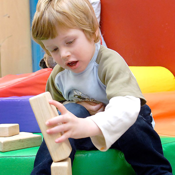 Young boy stacking wood blocks